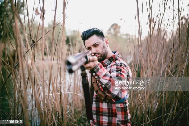 沼で獲物に彼の武器を目指す現代の男性ハンター