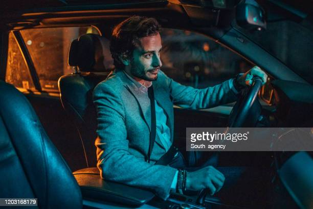 modern man driving a car in city at night - smart casual stock pictures, royalty-free photos & images
