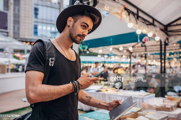 modern man holding book and text messaging - tradeshow stock pictures, royalty-free photos & images