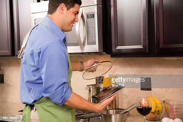 Modern man prepares meal. Home kitchen. Digital tablet online recipe.