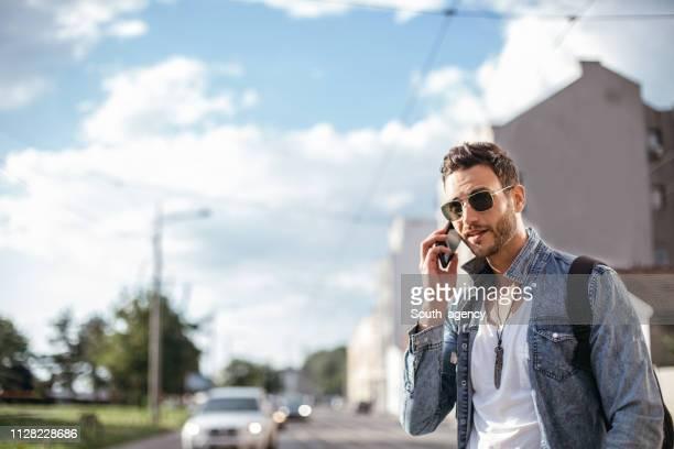 hombre moderno hablando por teléfono móvil en la calle - un solo hombre joven fotografías e imágenes de stock