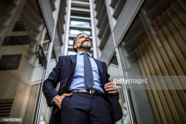modern mature businessman leaving work place - mani in tasca foto e immagini stock