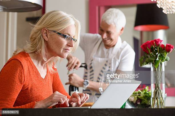 Modern Mature Couple Preparing Food and Working on Laptop