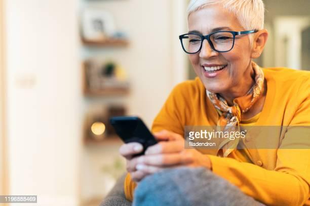 現代の成熟した女性のテキストメッセージ - 年配の女性一人 ストックフォトと画像