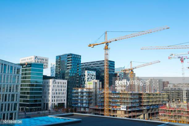 modern mega construction site in oslo with cranes behind the opera house