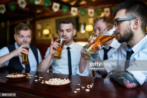 homens modernos, apreciando o sabor da cerveja - comida de pub - fotografias e filmes do acervo