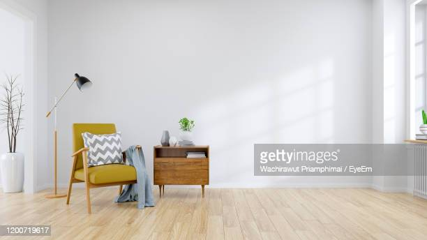 modern mid century and minamalist interior of living room yellow armchair with wood table - muur stockfoto's en -beelden