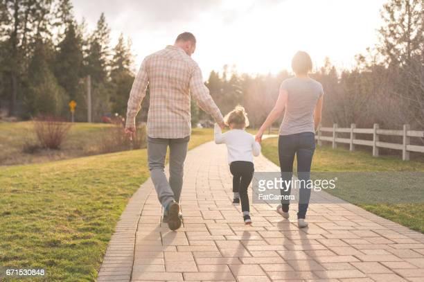 Moderne et maman marche main dans la main avec leur jeune fille sur le trottoir