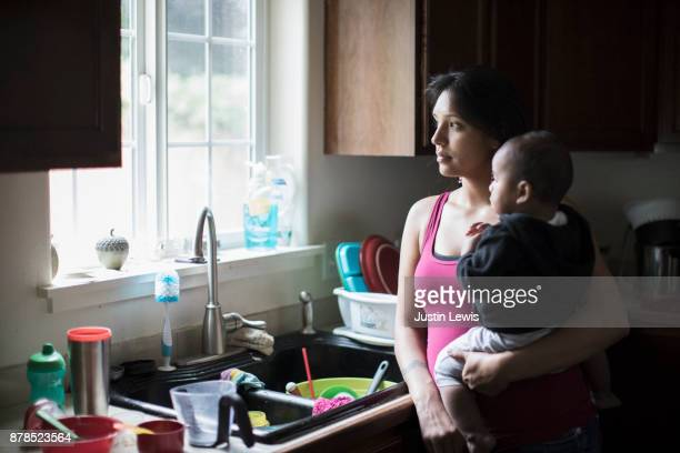 Modern Native American Mother and Baby Share a Cuddly Moment While Doing Dishes in the Kitchen