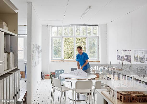 A modern office. A man looking at plans at a table, architectural drawings. Building models on shelves. Open windows. Summer.