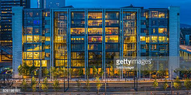 Modern office building illuminated interior against blue dusk Oslo Norway