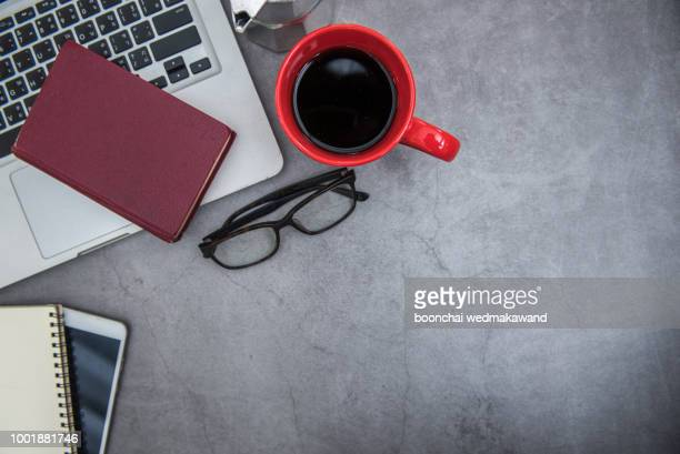 modern  office desk table with laptop, smartphone and other supplies with cup of coffee. blank notebook page for input the text in the middle. top view, flat lay. - office desk top view stock photos and pictures