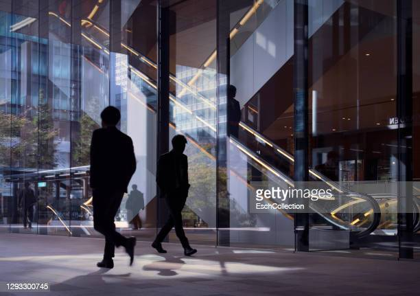 modern office facade with silhouettes of passing office workers - commuter stock pictures, royalty-free photos & images