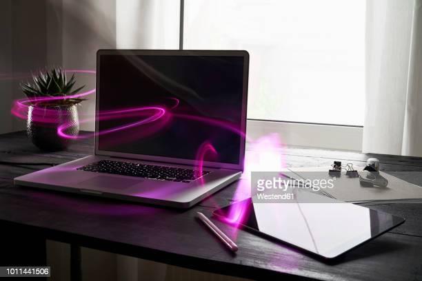 modern office with laptop and digital tablet on desk - computeranlage stock-fotos und bilder