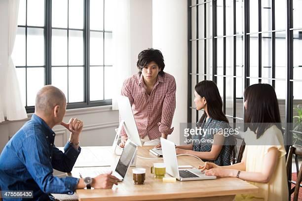 近代的なオフィスの仕事仲間とブレーンストーミング