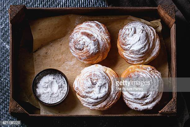 Modern pastries cruffins, whole and slice, like croissant and muffin with sugar powder, served in wooden box on black textil napkin over dark texture background. Top view