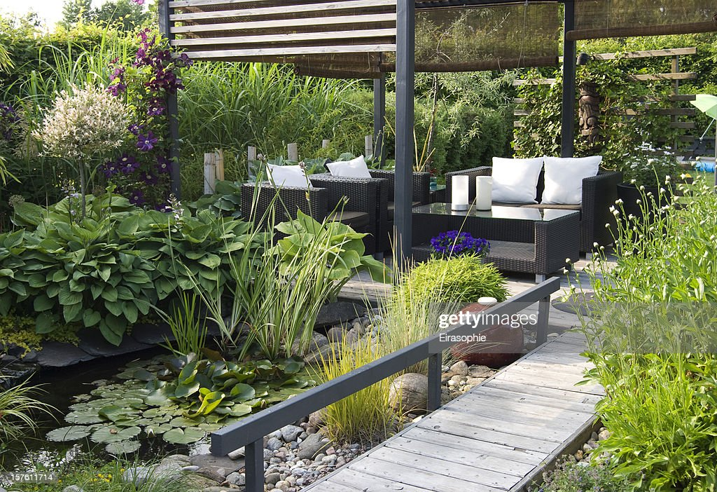 Modern patio garden lounge with a pond and outdoor sofas : Stock Photo