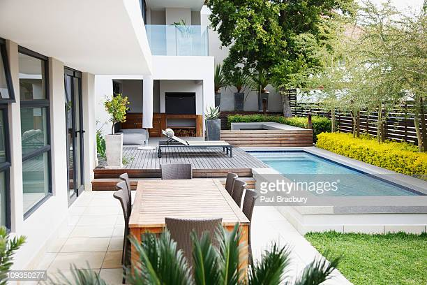 modern patio next to swimming pool - outdoors stock pictures, royalty-free photos & images