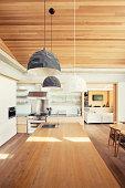 Modern pendant lights over long wood kitchen island