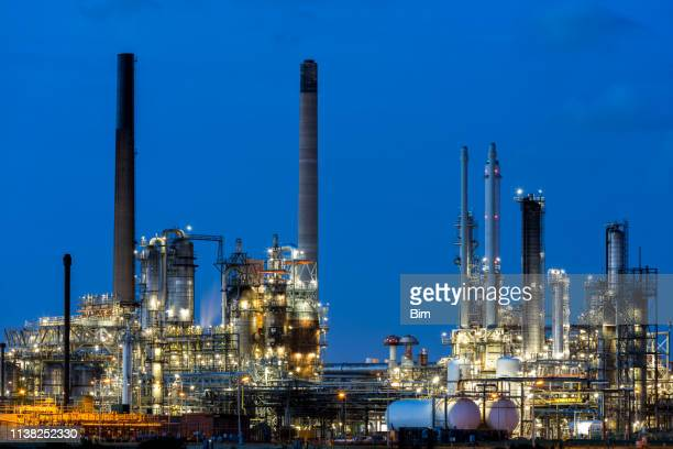 modern petrochemical plant illuminated at dusk - oil stock pictures, royalty-free photos & images