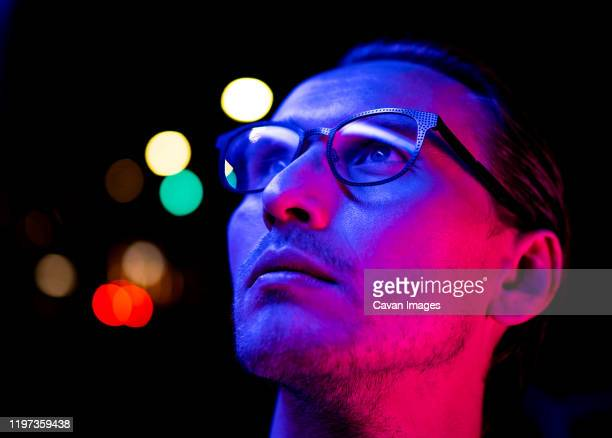 modern red and blue light portrait of a young man in glasses - マゼンタ ストックフォトと画像