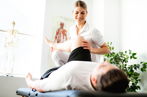 A Modern rehabilitation physiotherapy woman worker with client 1098314652
