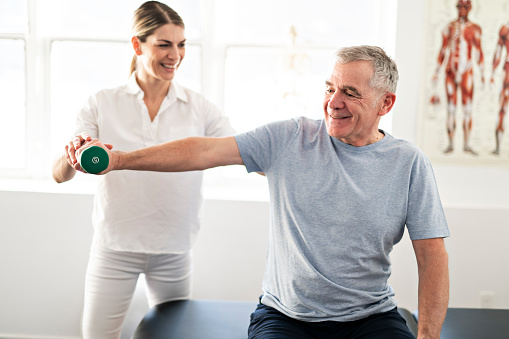 A Modern rehabilitation physiotherapy worker with senior client 1098314702