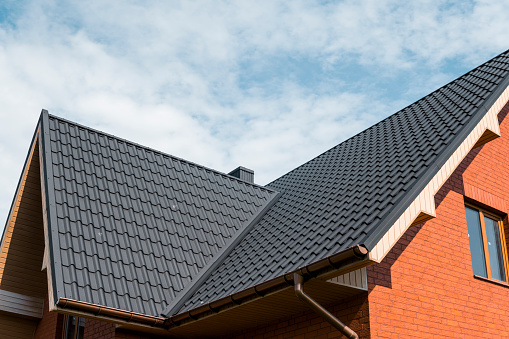 Modern roof covered with tile effect PVC coated brown metal roof sheets. 1018835072