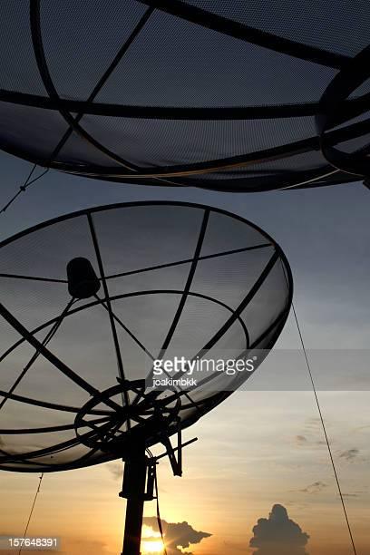 Antenne satellite moderne contre un ciel bleu au coucher du soleil