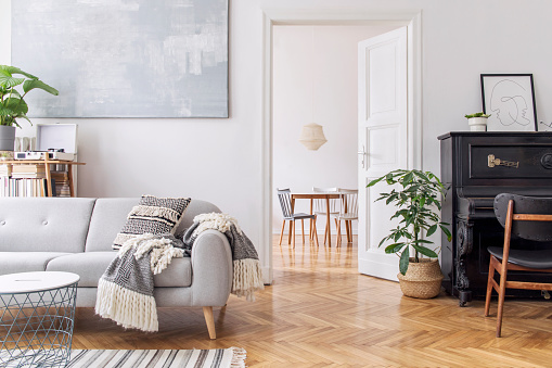 Modern scandianvian decor of living room with design sofa with elegant blanket, coffee table and bookstand on the white wall. Brown wooden parquet. Concept of minimalistic interior with piano. Mock up 1133193568