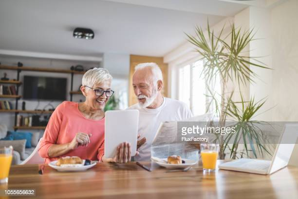 modern senior couple looking at newspaper and a tablet during breakfast - human settlement stock pictures, royalty-free photos & images