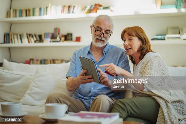 modern senior couple shopping online - medium shot stock pictures, royalty-free photos & images