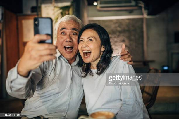 modern senior paar het nemen van een selfie in cafe - aziatische etniciteit stockfoto's en -beelden