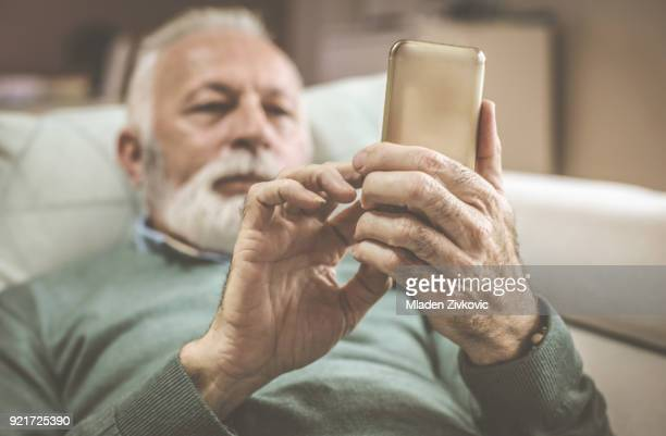 Homme senior moderne avec téléphone portable.