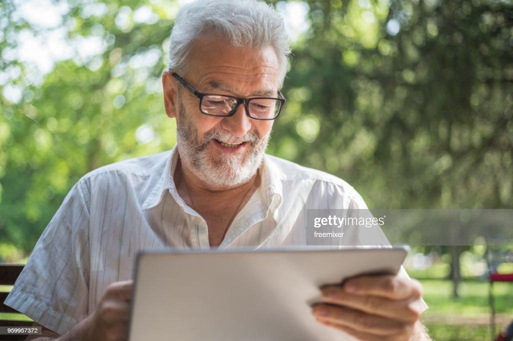 Der moderne senior Mensch mit tablet : Stock-Foto
