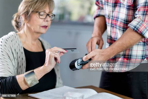 modern senior woman paying cashless with her credit card