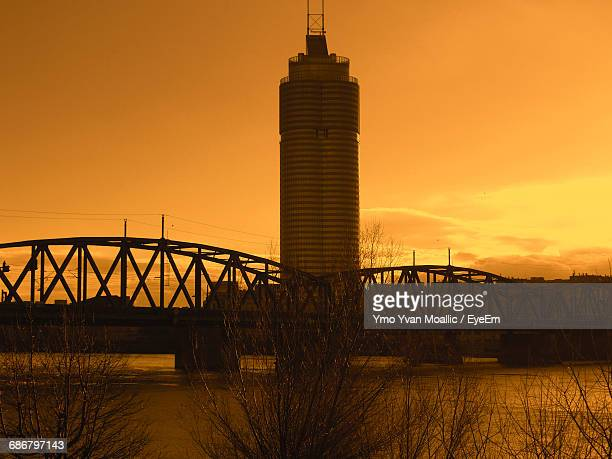 Modern Skyscraper By Bridge Over River Against Orange Sky During Sunset