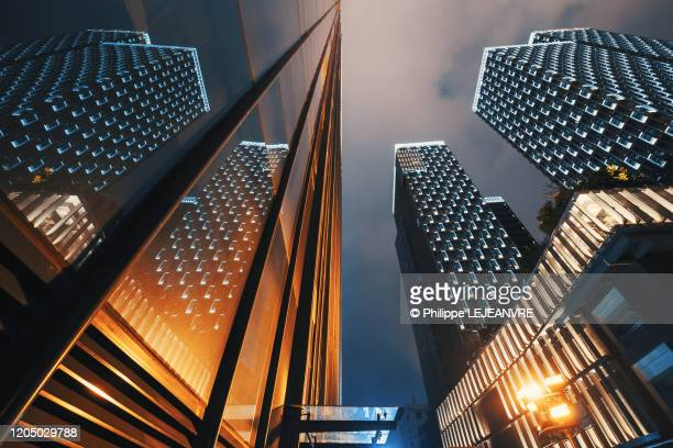 modern skyscrapers illuminated at night reflecting on a glass facade low angle view - skyscraper foto e immagini stock