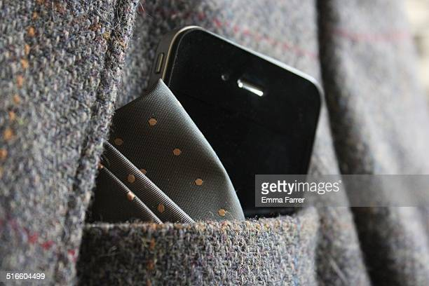 Modern smartphone phone next to a spotted silk handkerchief in the breast pocket of a gentleman's old fashioned tweed jacket