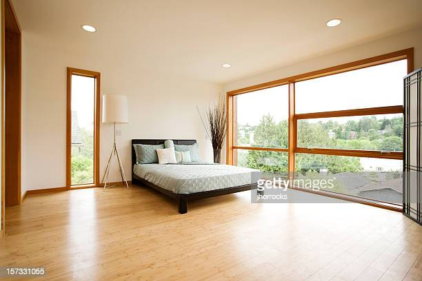 modern spacious bedroom with hardwood floors - bamboo stock photos and pictures