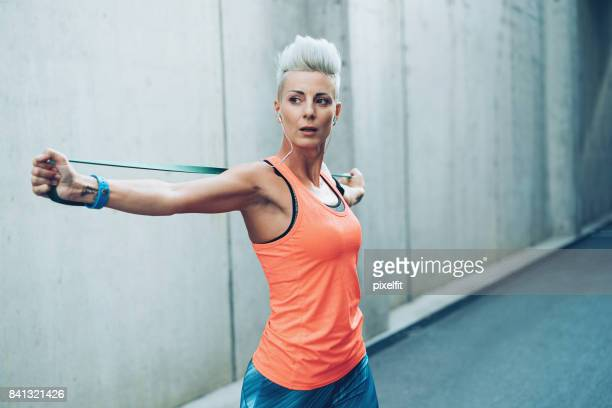 Modern sportswoman exercising with resistance band