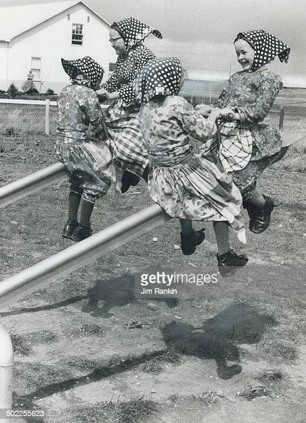 Modern steel teetertotter provides amusement for Hutterite girls during recess Their clothes in the style of 18thcentury Europe and their boots are...