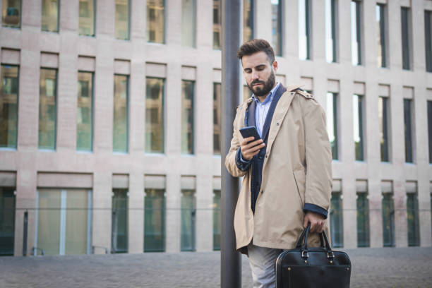Modern stylish middle eastern businessman lawyer with breifcase checking mobile phone app standing on office area