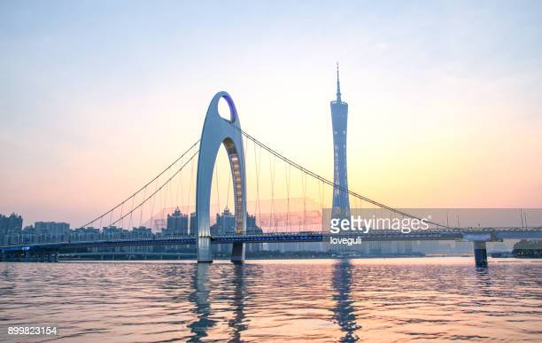 modern suspension bridge over river at sunset - guangdong province stock photos and pictures