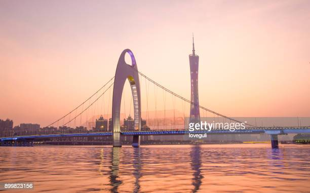 modern suspension bridge over river at sunset