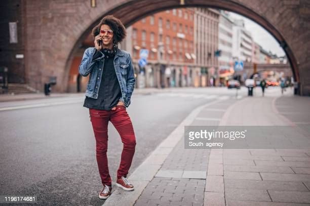 modern talking on mobile on the street - black jacket stock pictures, royalty-free photos & images