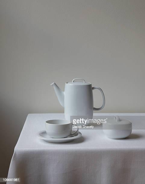 modern tea/coffee set on white linen table. - ティーポット ストックフォトと画像
