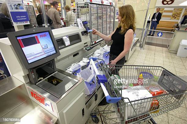 Modern technique makes it happen shopping without cashier Young woman is paying her shoppings with an eurocard at a new type of till where the...