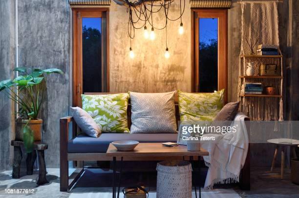 modern tropical living room at night - abenddämmerung stock-fotos und bilder