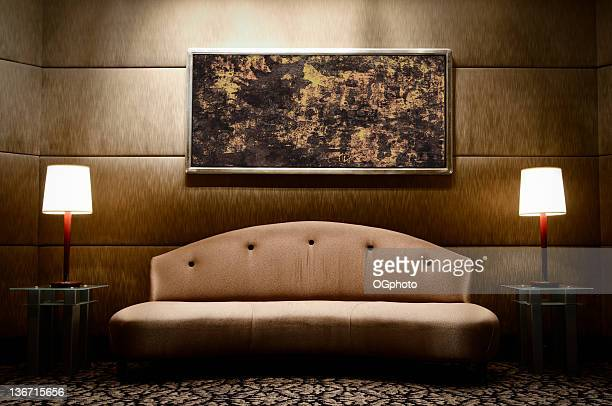 Modern upholstered sofa, flanked by matching lamps and art